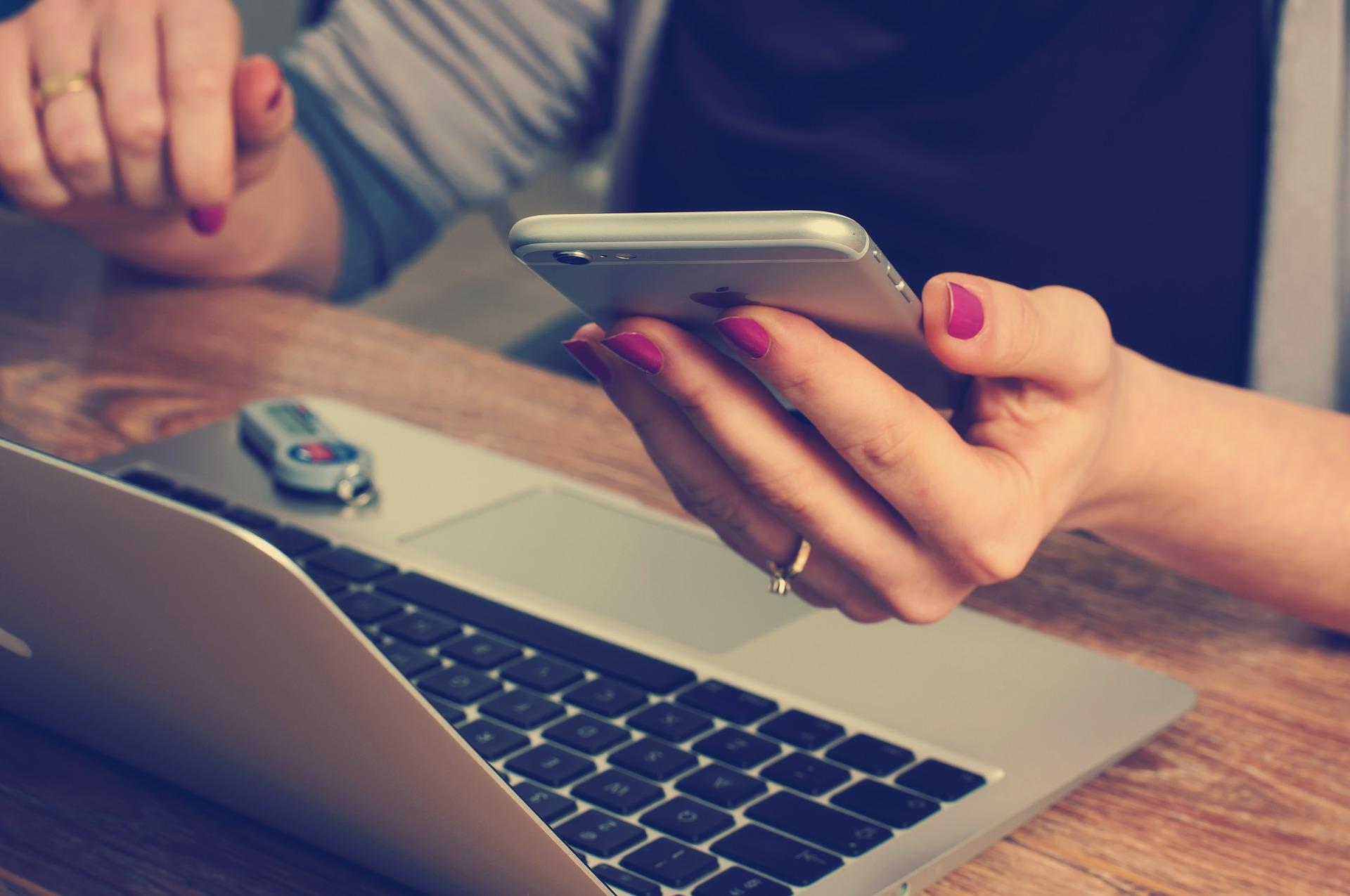 Kobiet ze smartfonem i laptopem porównuje oferty prądu dla firmy